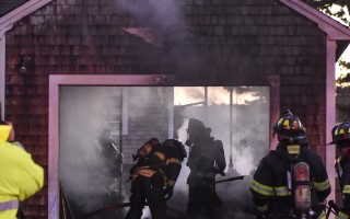 Firefighters from several area departments work to extinguish a garage fire on Fresh Water Road in Harwich on Monday night. No one was injured but the garage was destroyed.  (photo: )