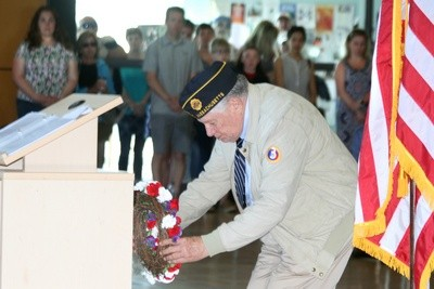 Donald Grunewald places a wreath at the podium to honor his late cousin, who died in World War II.