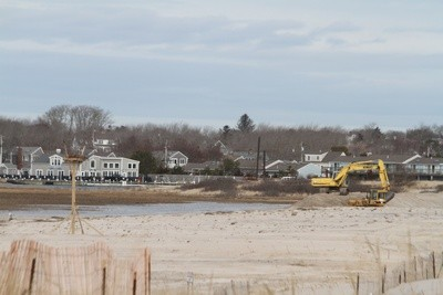 An excavator piles sand on Quitnesset Spit between Morris Island and Outermost Harbor Monday.  A dredge was expected to begin work this week.  ALAN POLLOCK PHOTO