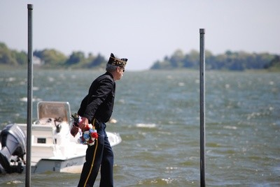 Tony Gibson tosses a wreath into the waters of Town Cove to honor those who lost their lives at sea.