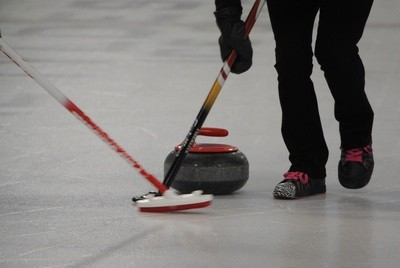 "Brooms try to sweep the stone to the proper spot on the ""field of ice."""