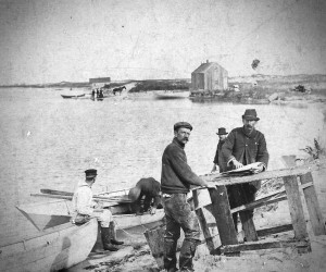 Ellis brothers, Albert and Robert, at fish splitting table on the shore of the Powder Hole, Monomoy Point, circa 1890. In the background a new lighthouse keeper and his family land to assume the charge of the Monomoy Point Lighthouse. Photo taken from the Chatham Historical Society Collection, given to CHS by Ann and Harry Ellis.  (photo: )