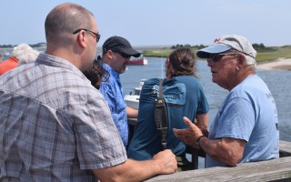 Fred Bennett, right, is one of several retired fishermen who staff the Alliance's Pier Host program. Three days a week they are stationed at the fish pier observation deck where they explain to visitors how the town's commercial fishing industry works and what species are being unloaded at the pier. TIM WOOD PHOTO  (photo: )