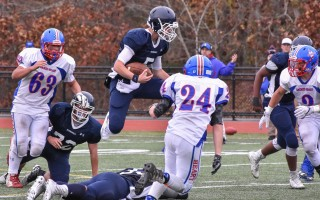 Quarterback Ryan Downs (5) leaps over teammate Jake Wisniewski en route to a Monomoy first down.  KAT SZMIT PHOTO  (photo: Kat Szmit)