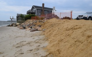 Newly deposited sand provides a narrow buffer between Nantucket Sound and the parking lot at Cockle Cove Beach. Officials hope the buffer holds until planned dredging later in the year can provide a larger volume of sand to build up the beach. TIM WOOD PHOTO  (photo: )