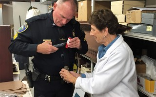 Chatham Police Sergeant William Glover examines a World War I-era grenade with Atwood House and Museum's Janet Marjollet, head of the costumes and textiles department. COURTESY PHOTO  (photo: )