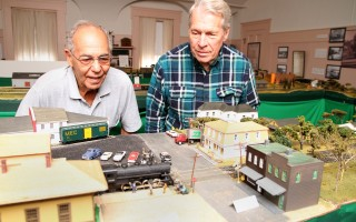 Ross Hall of the Nauset Model Railroad Club (right) and Harwich Historical Society volunteer Al Raneo watch as a locomotive lumbers through downtown Orleans.     (photo: Alan Pollock)