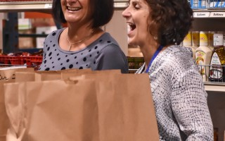 Family Pantry volunteers Jen Eldredge and Debbie Nixon share a laugh with a client while making sure their bags are full. KAT SZMIT PHOTO 