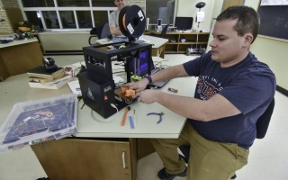 Jesse Craig of Eastham removes printed materials from a 3D printer that's part of the Cape Cod Makers new space at the Harwich Cultural Center, while fellow maker Jim Sullivan looks on. Kat Szmit Photo  (photo: )