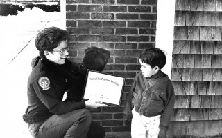 Three-year old Tyler Proudfoot was honored for alerting his parents to a smoldering fire in their home. He was presented a National  Fire Protection Association certificate for his actions by firefighter Kate Maguire and her sidekick, Barney the Bear.  1993. FILE PHOTO  (photo: )