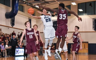 Monomoy's Nick Meehan (22) shoots past the defensive arm of Dedham's Juran Ligonde (35) during tournament play at MRHS on Tuesday night. Kat Szmit Photo  (photo: )