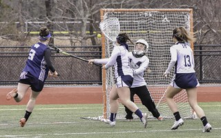 Monomoy goalie Maddy Flaherty fends off a shot from Nantucket's Nina Wilson (3) with assistance from Kelsey Olson (1) and Izzy O'Donnell (13) during game play at MRHS on March 29. Kat Szmit Photo  (photo: )