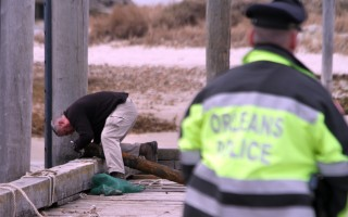 A technician from the State Police Bomb Squad examines the ordnance dredged up from Cape Cod Bay Wednesday morning. ALAN POLLOCK PHOTO  (photo: Alan Pollock)
