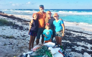The Swain family with a pile of debris cleaned from the beach at Long Island in the Bahamas.  (photo: )
