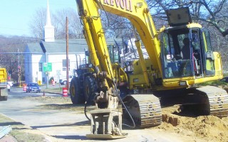 With Orleans United Methodist Church as a backdrop, a Revoli Construction excavator forms its own steeple on Main Street. First-phase sewer main work in the downtown area was completed on the day town meeting voted to approve $4.2 million for further water quality work. The spending is subject to a debt exclusion vote May 15.  ED MARONEY PHOTO  (photo: Ed Maroney)