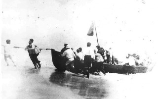 With a hand from the U.S. Coast Guard, members of the crew of the tug Perth Amboy and its barges come ashore at Nauset Beach in 1918, survivors of a U-boat attack. ORLEANS HISTORICAL SOCIETY PHOTO  (photo: Courtesy Orleans Historical Society)