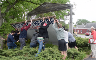 Monomoy Theatre students put up the Main Street stage's sign Sunday under the watchful eye of Artistic Director Alan Rust. TIM WOOD PHOTO  (photo: )
