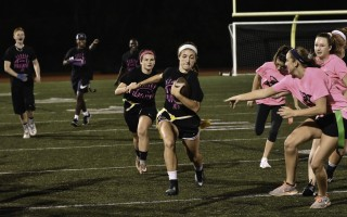 Senior Abby Wallace keeps up a strong pace even while ducking away from a potential flag-grabber during the Powderpuff game, as teammate Katie Ganshaw lends support and senior coaches Chris Hall, Kyle Charlot and Chevar Shakespeare cheer her on. Kat Szmit Photo  (photo: )