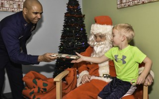 Rain couldn't keep Santa away from his post at the Chatham Community Center on Sunday afternoon, and neither did it prevent Bo Brebbia from hopping on his lap and sharing his Christmas wishes before receiving a festive candy cane and a special gift from Officer in Charge of Coast Guard Station Chatham, Senior Chief Boatswains Mate Carlos Hessler.  KAT SZMIT PHOTO 
