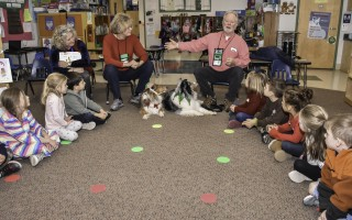 Tom and Jane Wilson, owners of therapy dogs Toffee and Garbo, tell students at Harwich Elementary School about the dogs and what they can do, including helping kids feel safer in a learning environment. 