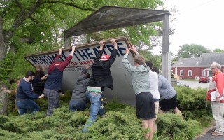 Students work together to put up the Monomoy Theatre sign last June, a ritual at the start of each summer's season. Artistic Director Alan Rust is on the right. Theater supporters were working this week to put together an offer to buy the downtown property. FILE PHOTO  (photo: )