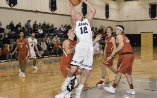Monomoy's Jamie Routhier takes to the air for two points for the Sharks against the Barnstable Red Raiders in their final regular season game on Feb. 21. Kat Szmit Photo  (photo: )
