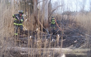 Firefighters from Eastham dig into the remains of a brush fire off Bridge Road in Orleans.  ED MARONEY PHOTO  (photo: Ed Maroney)