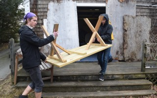 Reid Williams, left, and Mark Lawrence move a picnic table out of one of the Monomoy Theatre buildings. Both were actors in last year's company. TIM WOOD PHOTO  (photo: Tim Wood)