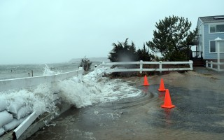 A storm surge pushes through a sandbag berm at the end of Starfish Lane during one of last March's coastal storms. FILE PHOTO  (photo: Tim Wood)