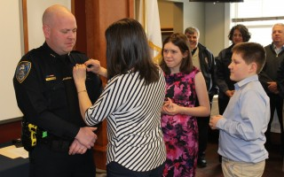 Nichole Considine pins the badge on her husband, newly named Harwich Police Department Deputy Chief Kevin Considine, while daughter Abigail and son Michael look on during a swearing-in ceremony at the police station on Friday. WILLIAM F. GALVIN PHOTO  (photo: William F. Galvin)