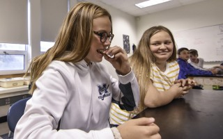 As Alana Lojko gives a sour cream and onion cricket a try, classmate Isabella  Coomber makes a face. Entomologist Larry Dapsis brought the insects and a program about insect-based diets to Julia Randall's class at Monomoy Middle School. (photo: )