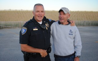 "Old friends Kevin Higgins and Fire Chief Tony Pike embrace at Nauset Beach. ""My people made me gray,"" Higgins said. ""His people made him bald.""  BARRY DONAHUE PHOTO  (photo: Barry Donahue)"