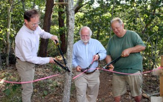 Using loppers for the job, (from left) Michael Lach of the Harwich Conservation Trust and Selectmen Don Howell and Ed McManus snipped the ceremonial ribbon opening the Cornelius Pond Woodlands Monday.  (photo: Alan Pollock)