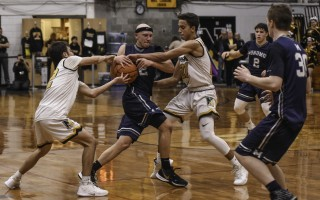 Monomoy's Jamie Routhier (12) fights for possession against Nauset's Bobby Joy (12 white) and Keleb Daniels (21) as Aidan Melton (30) and Elijah Beasley (2) look to lend support during game play on Dec. 13. Kat Szmit Photo  (photo: )