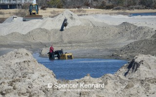 A bulldozer operator waits to be picked up after his machine ran into soft sand and slid down an embankment at the dredge de-watering pond being used in the Outermost Harbor dredging project. No one was hurt and the bulldozer was pulled out of the water, cleaned up and is back in operation. SPENCER KENNARD PHOTO  (photo: )