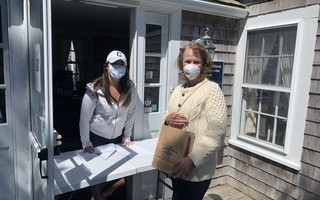 The Chatham Chamber of Commerce and Chatham Merchants Association handed out bags of 10 complimentary disposable face masks and bottles of hand sanitizer donated by Dirty Water Distillery in Plymouth to their members last week to prepare for the next reopening phase. Chamber executive director Mary Cavanaugh said Sandy Wycoff, owner of the Chatham T Co. secured the donation. Here chamber volunteer Molly Cavanaugh hands a bag to Joanne Doggett, co-owner of Where the Sidewalk Ends Bookstore. AMY TAGLIAFERRI PHOTO  (photo: )