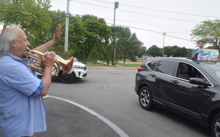 Music teacher Frank Toppa played tunes and waved as students drove by with their families.  (photo: )