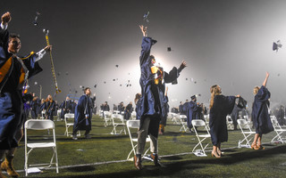 Members of the Monomoy Regional High School Class of 2020 toss their caps into the air at the end of Tuesday night's long-awaiting graduation. The event was held under the lights at the school's sports turf, where socially distanced students heard pre-recorded speeches and received awards and scholarships. KAT SZMIT PHOTO  (photo: Kat Szmit)