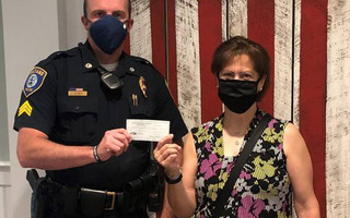 Sgt. Pat Cronin of the Orleans Police Department presents Lisa Simundson, office manager of the Orleans Chamber of Commerce, with a donation toward the new Hardship Fund aimed at helping small businesses in Orleans defray costs during the pandemic. COURTESY PHOTO 
