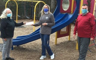 Harwich Fund member Dr. Bonnie Scott presents Abby Newberry-West, director of The Children's Center, with funds to assist with the expansion of the playground at the center. Harwich Fund Chair Brian Scheld is on the right. COURTESY PHOTO  (photo: )