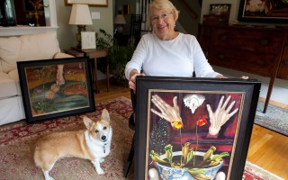 Sydney Lewis Glover is photographed in her home in Chatham, MA, with a few of the surrealist paintings she and her husband found under her mother's bed when she died in 1995. Sydney's mother, Doris Lindo Lewis, who created the paintings, is since being recognized as one of the first female surrealist painters. Left is Sydney and her husband's corgi,