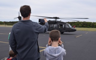 "A youngster covers his ears as a Blackhawk helicopter prepares to take off at the Chatham Airport open house held Saturday. ""Planes, Trains and Automobiles"" was the theme of the event, which featured vintage planes, antique cars, sea planes and model trains. Folks could also take sightseeing flights and participate in a fundraising raffle. TIM WOOD PHOTO 