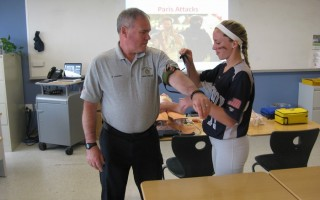 Paramedic Rob Sanders from the Harwich Fire Department visited wellness classes recent. He shared summer safety tips and the importance of learning CPR/AED and first aid. Here, Carly Tolley is applying a tourniquet to the paramedic.  (photo: )