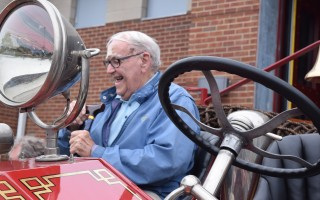 Ben Goodspeed takes a short ride on the Chatham Fire Department's antique Maxim engine at the recent dedication of the town's new fire station. TIM WOOD PHOTO  (photo: )