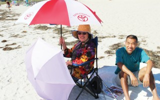 Hanna Chu, under her umbrella, and Zhiping Wei of Nashua, N.H. came to enjoy the Nantucket Sound waters, more so than the sun on the first day of fall.  (photo: )