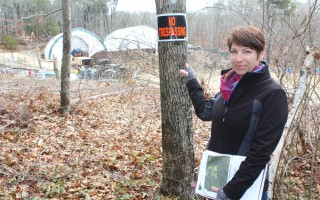 "Abutter Audrey Greenway points to the ""no trespassing"" sign attached to the tree just over her property line. Greenway is concerned with the expansion of Resilient Family Farm off Chatham Road in a heavily residential neighborhood. WILLIAM F. GALVIN PHOTO  (photo: William F. Galvin)"