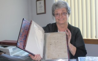 Town Clerk Anita Doucette holds one of the historic documents that helped shape this town. WILLIAM F. GALVIN PHOTO    (photo: William F. Galvin)