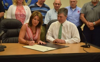 <Caption>As Chairman of Selectmen Cory Metters and other town officials look on, Lt. Gov. Karyn Polito signs the Commonwealth Community Compact between the town and state Tuesday. TIM WOOD PHOTO 