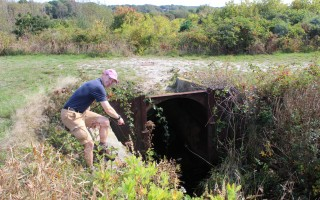 Harwich Conservation Trust Executive Director Michael Lach points to the types of structures in the Robert F. Smith Cold Brook Preserve that restrict the passage of fish heading to spawning grounds. WILLIAM F. GALVIN PHOTO  (photo: )