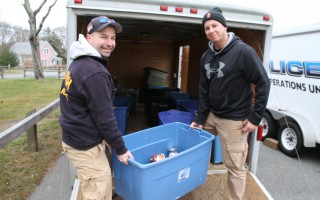 Harwich firefighters Brad Willis (left) and Kevin Duquette load totes of donated food into a trailer at Brooks Park. ALAN POLLOCK PHOTO  (photo: )